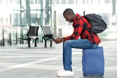 Young man sitting on traveling bag and using cell phone Royalty Free Stock Photo