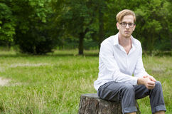 Young man sitting on a tree stump Stock Photography