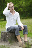 Young man sitting on a tree stump Stock Photos