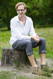 Young man sitting on a tree stump Royalty Free Stock Image