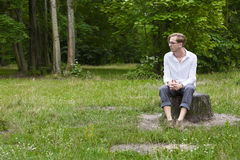 Young man sitting on a tree stump Royalty Free Stock Images