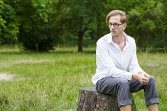 Young man sitting on a tree stump Royalty Free Stock Photo