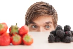 Young man sitting under table and looking at fruits. Royalty Free Stock Photos