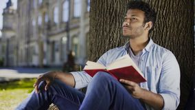 Young man sitting under tree reading book and thinking, fiction literature. Stock footage Royalty Free Stock Image