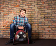 Young Man Sitting on Vintage Toy Vehicle Stock Photos