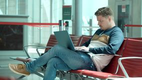 Young man sitting in waiting area of the airport with laptop. Young man sitting in waiting area of the airport and working on laptop stock video footage