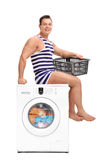 Young man sitting on a washing machine Royalty Free Stock Images
