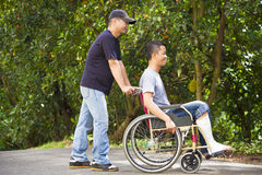Young man sitting on a wheelchair with his brother Stock Images
