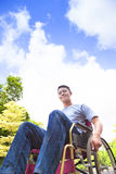 Young man sitting on a wheelchair with natural background Stock Images
