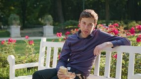 Young man having a snack in the park. A young man sitting on a white bench in the park and having a snack. Medium shot stock footage