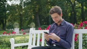 Young man in the park using a phone stock footage