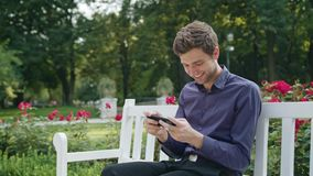 Young man in the park using a phone to play games stock footage