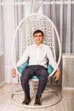 Young man sitting in white chair in bright room Stock Photo