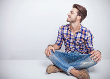 Young man sitting a white table with his legs crosed Royalty Free Stock Images