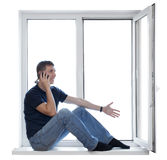 Young man sitting on window Royalty Free Stock Image