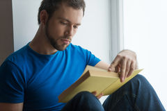 Young man sitting on window sill and reading. Royalty Free Stock Photography