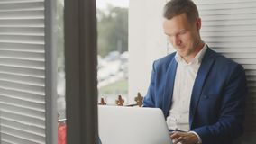 Young man sitting on windowsill having pleasant conversation. Young man sitting on windowsill having pleasant online conversation and smiling. Office manager stock video footage