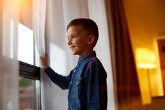 Young man is sitting on windowsill and looking out at sunset stock photography