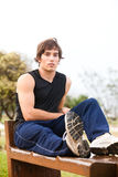 Young Man Sitting on Wooden Bench Royalty Free Stock Image