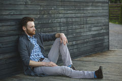 Young man sitting on the wooden floor Royalty Free Stock Photography
