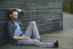 Young man sitting on the wooden floor Stock Photos