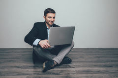 Young man sitting on wooden floor, using laptop. Communication concept stock photos