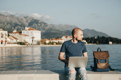 Young man sitting and working with laptop computer near the sea.  Royalty Free Stock Images