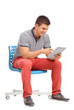 Young man sitting and working on a tablet Stock Image