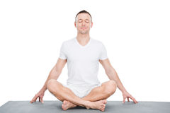 Young man sitting on yoga mat and meditating in lotus position Stock Photos