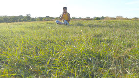 Young man sitting in yoga pose at green grass in the meadow and meditates. Muscular guy relaxing in lotus pose at nature. Recreation outdoor at sunny day Royalty Free Stock Photos