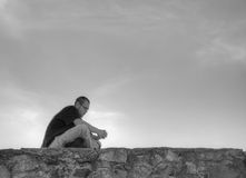 Young man sittting outdoors Stock Photos
