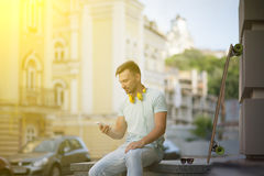 Young man with skate-board. Man sitting in the centre of European city. Short-haired man in light T-shirt with yellow earphones searching telephone number. Toned Royalty Free Stock Photo