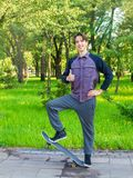 Young man with skateboard in city park. Teen boy skater. Young man standing on skateboard in city park. Teen boy skater stock photo