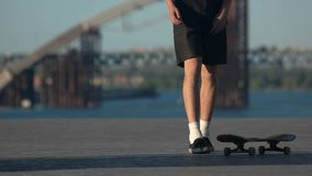 Young man with a skateboard. Legs moving in slow-mo. Sport for risky people. Vibe of the youth stock footage