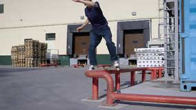 Young man on skateboard riding above metal fence on street stock video footage