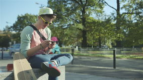 Young man with skateboard texting on cell phone in a city.