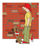 Young man with skateboard. Wearing a baseball cap and sneakers, standing near a brick wall Stock Photos