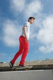 Young man skateboarding with blue sky background Stock Images