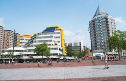 Young man skateboards through Blaak Square. ROTTERDAM, HOLLAND -AUGUST 22, 2017; Young man skateboards through Blaak Square while people gather or cycle enjoying Stock Photo