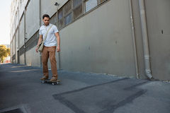 Young man skating on footpath by building Royalty Free Stock Image