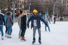 Young man skating at a public ice skating rink outdoors in the city center. Stock Photo