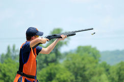 Young man skeet shooting with airborne shell Royalty Free Stock Photos