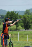 Young man skeet shooting with airborne shell. Young man skeet shooting/trap shooting with airborne shell Stock Photo