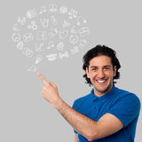 Young man with sketchy icons. Smiling man showing set of business icons stock illustration