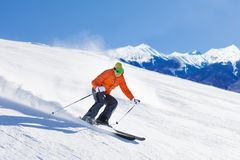 Young man in ski mask sliding fast while skiing. View during sunny winter day on Krasnaya polyana ski resort and Caucasus mountains in Sochi, Russia Royalty Free Stock Photo