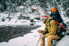 Young man with ski sitting in the snow fores. T near the mountain river Stock Image