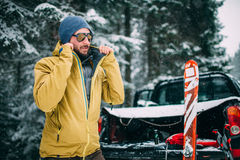 Young man with ski in the snow forest. Standing near the car Stock Photo