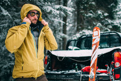 Young man with ski in the snow forest. Standing near the car Royalty Free Stock Image