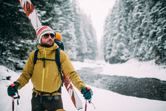 Young man with ski walking in the snow forest. Near the mountain river Stock Photo