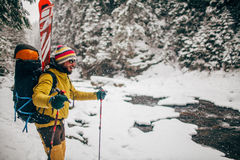 Young man with ski walking in the snow forest. Near the mountain river Stock Image